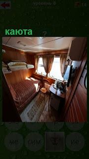 небольшая каюта на судне с иллюминаторами и диваном