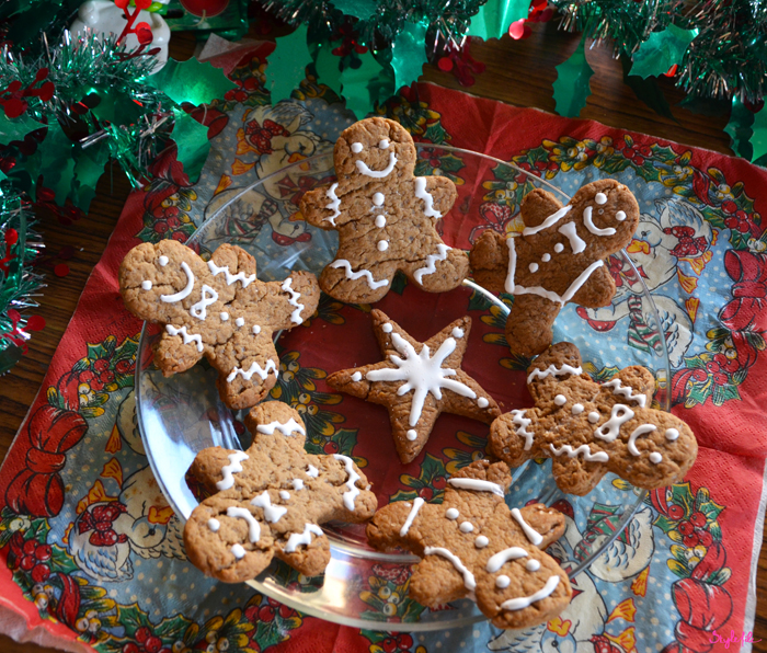 A plate of gingerbread men cookies decorated with royal icing frosting placed on a glass plate in the midst of mother goose napkin and christmas tinsel decor