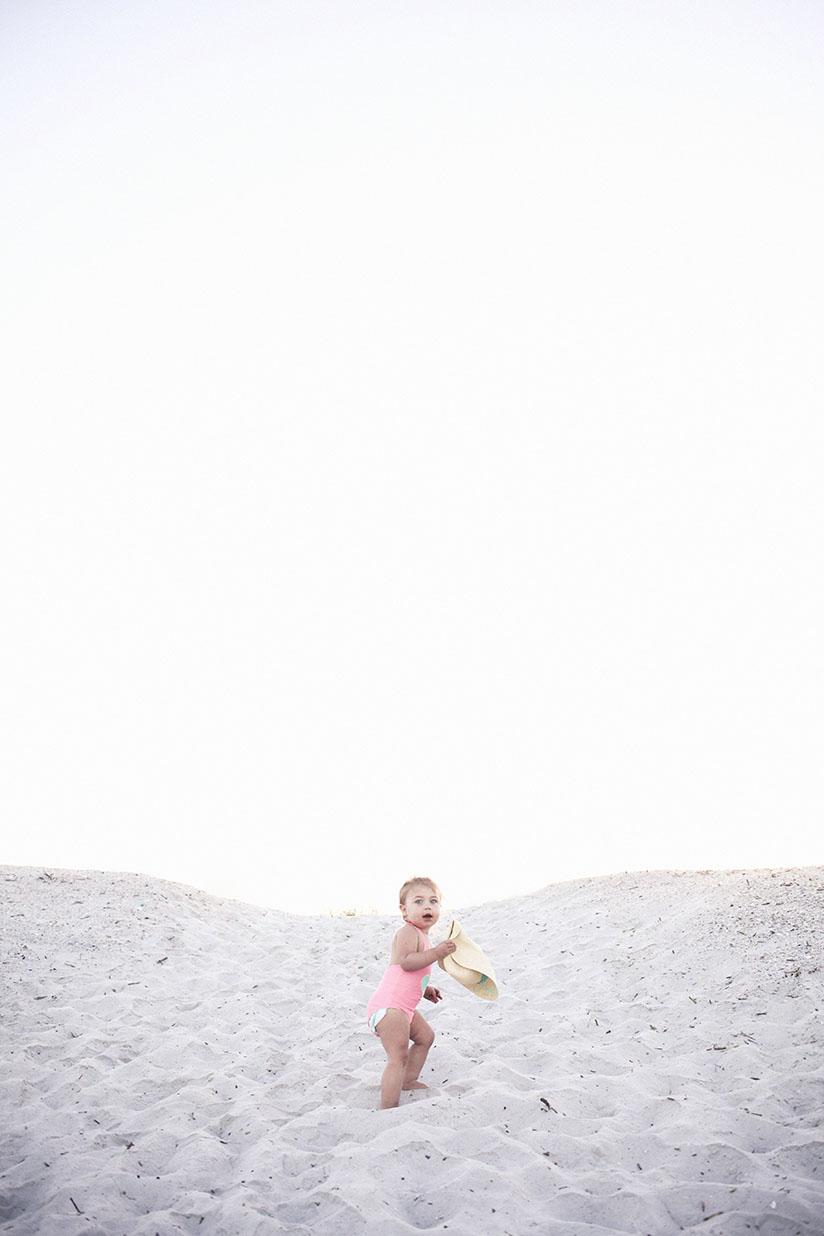 Little girl climbing dunes in Sunuva swimwear