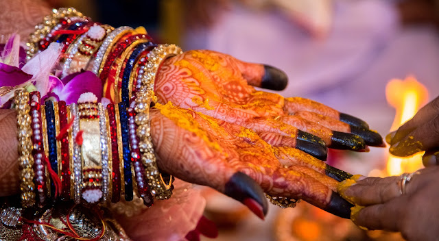 Bride's Hands and Other woman rubbing ubtan on them
