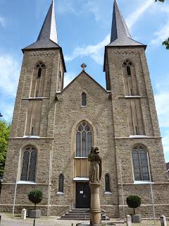 Eine Kirche mit zwei Türmen, davor eine Statue