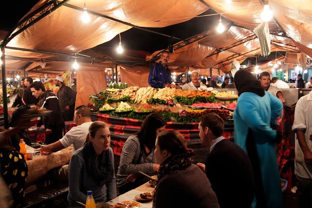 Gente comiendo en los puestos de comida nocturnos de la plaza Jemaa el-Fna de Marrakech