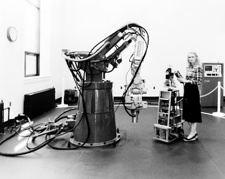 A black and white image of a woman wearing a skirt and blouse holding the controls of a machine that stands as high as her shoulder. It is made of metal and has several shelves and wires. Standing higher and wider than both of them is a an arm-like machine screwed to the ground with large cables running from it. They appear to be in a laboratory.