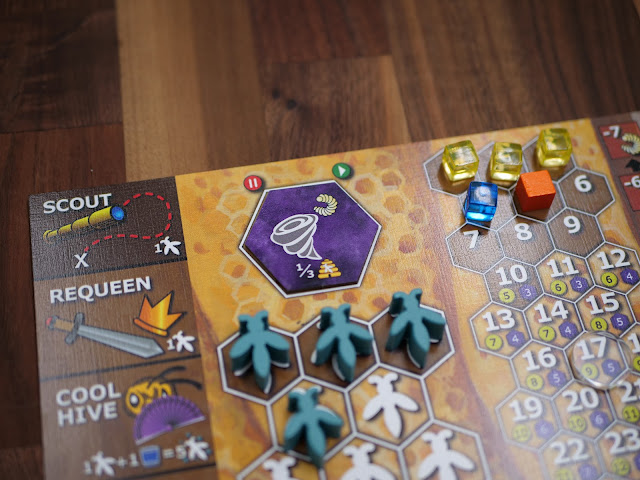 "The Bee Lives board with bee meeples on it, including the hexagons they land in and signs for swarming, scouting, requeening, and ""cool hive"""