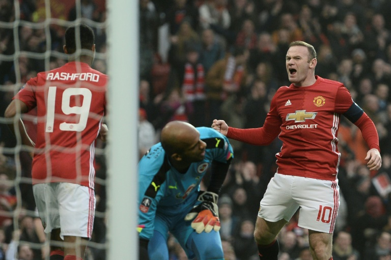 Wayne Rooney (right) celebrates after equalling Bobby Charlton's Manchester United all-time scoring record during the English FA Cup third round match against Reading at Old Trafford on January 7, 2017