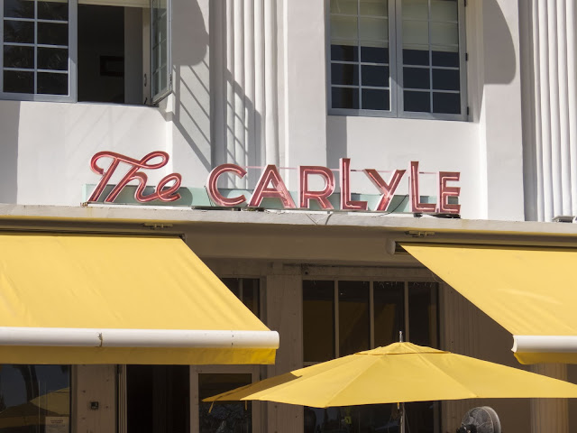 Neon sign and yellow umbrellas at the Carlyle in the Miami South Beach Art Deco Historic District