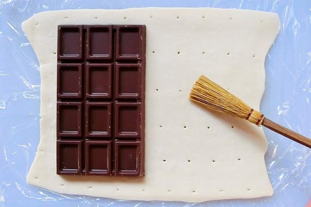 冷凍パイシートの上に板チョコレートを置き、空いている生地の上に溶き卵黄を塗る。