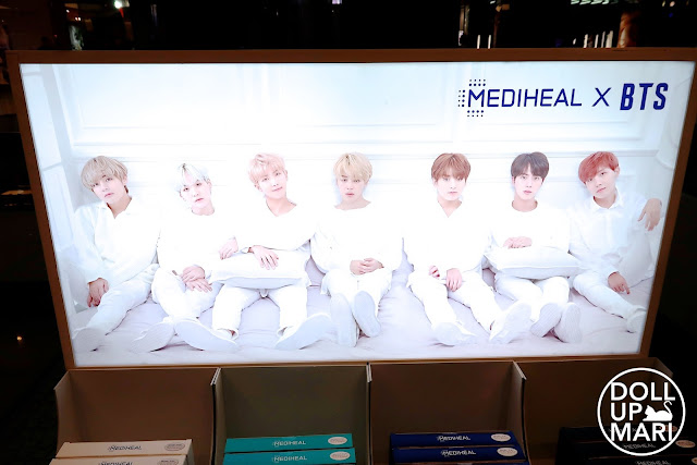 Mediheal X BTS In White Outfits In Light Up Panaflex Signage