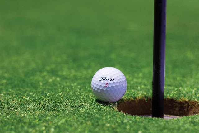 A ball falls into the hole center cut