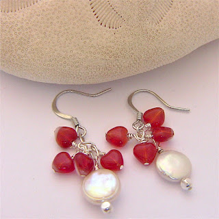 white pearl earrings with tiny red hearts