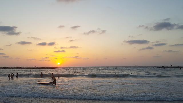 רוחצים בחוף גורדון כשהשמש שוקעת