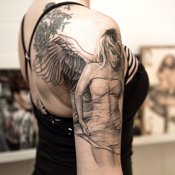Un mujer en camiseta de tirantes , vemos en su hombro derecho el tatuaje de un angel de la guarda, el tatuaje en 3d