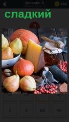На столе миска с фруктами, рядом сыр и сладкий мед в запечатанной банке