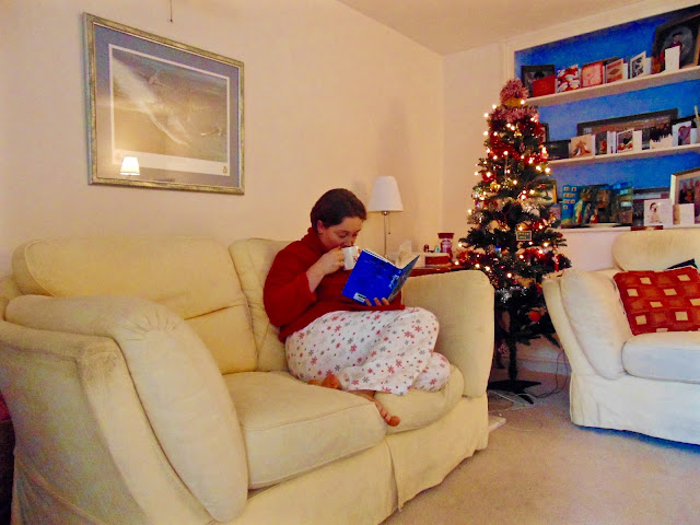Katy chilling out in her pyjamas with a cup of fruit tea and a good book.