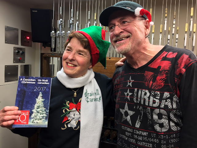Andrea poses with Pierre and the program for the Stairwell Carollers 40th Christmas concert season