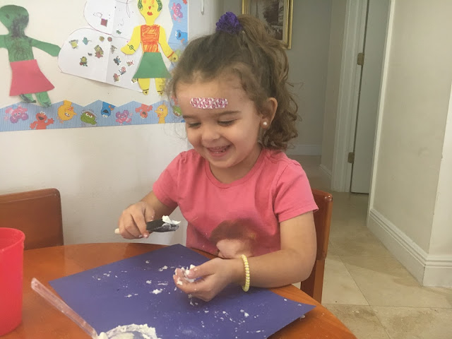 Little girl smiling while playing with fake snow at a table with a sheet of blue cardstock in front of her.