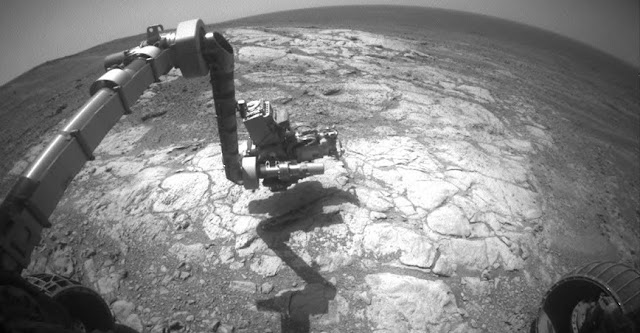 "NASA's Mars Exploration Rover Opportunity has extended its robotic arm for studying a light-toned rock target called ""Athens"" in this image from the rover's front hazard avoidance camera.  The camera recorded this image during the 3,970th Martian day, or sol, of Opportunity's work on Mars (March 25, 2015). This camera is mounted low on the rover and has a wide-angle lens. Image Credit: NASA/JPL-Caltech"