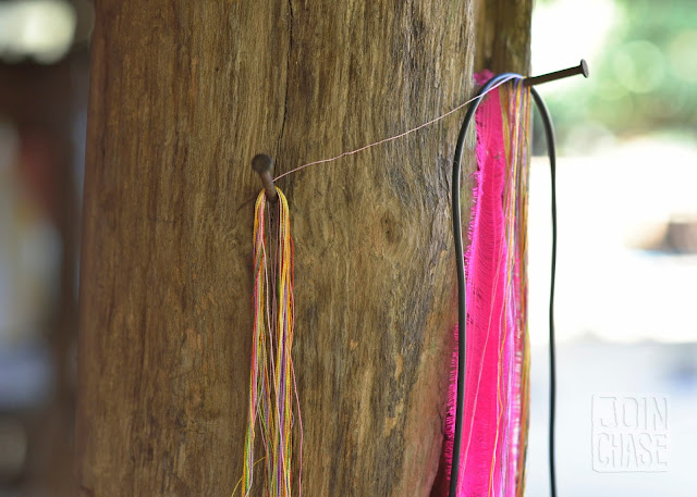 Thread hanging from a post near a loom in Sagaing Division, Myanmar.