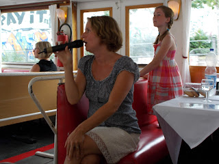 Pic of our seated tour guide with microphone providing commentary inside boat