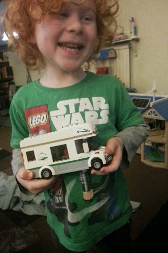 Four year old with first LEGO model following instruction booklet