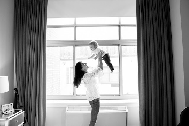 mom tosses her baby above her head by the window