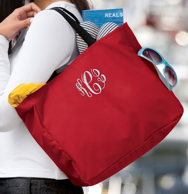 Lifestyle photo of model holding red bag with initials