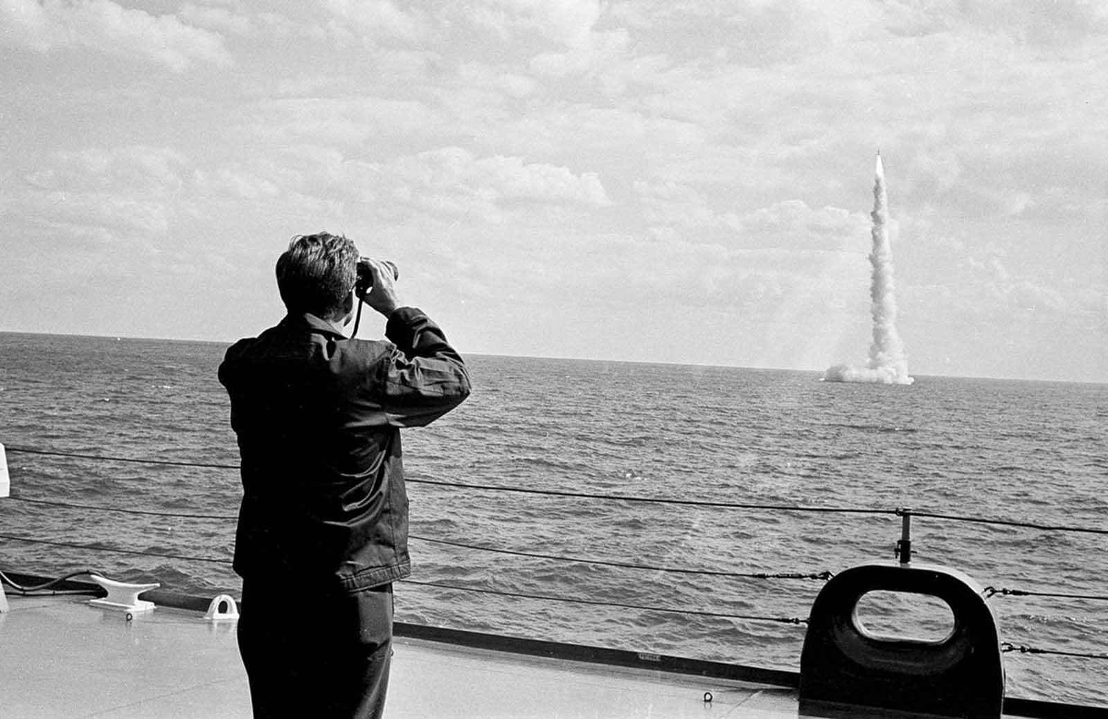 President John F. Kennedy, wearing a windbreaker, watches through binoculars as a Polaris missile clears the surface after firing from a submerged nuclear sub off Cape Canaveral, Florida, on November 16, 1963.