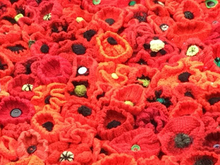 Close-up of a carpet of red, handmade crocheted poppies