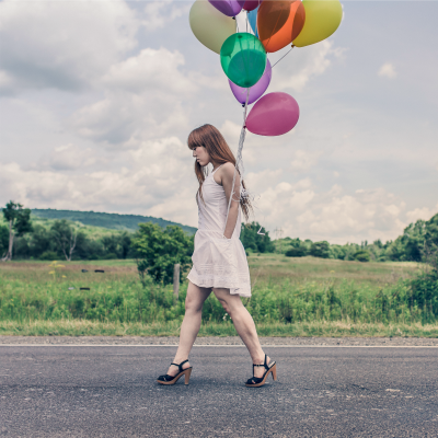 A woman walking down a country road holding multicoloured balloons