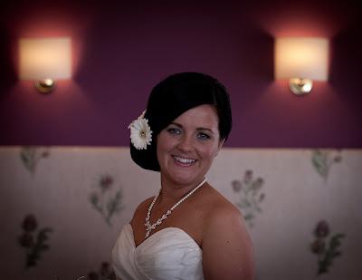 Side swept wedding bun with large flower detail