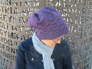 A woman wearing a deep purple worsted-weight knit hat. She is shown looking down towards the ground, you can see the top of the hat. The cable band is shown going around the head just above the ribbing. It is a Celtic knot style cable that runs end-to-end around the circumference of the hat. The top of the hat has gathers where the stitches were pulled in