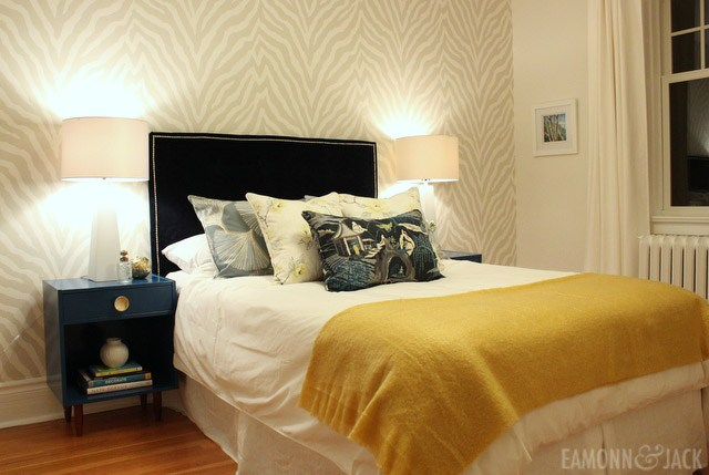 Bedroom with Etosha wallpaper and blue velvet headboard