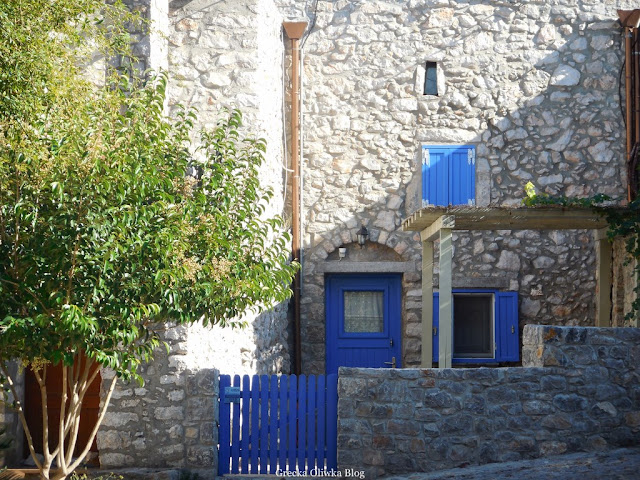 kamienny dom z niebieskimi okiennicami obok zielone liściaste drzewo grecka osada Avgonima Chios