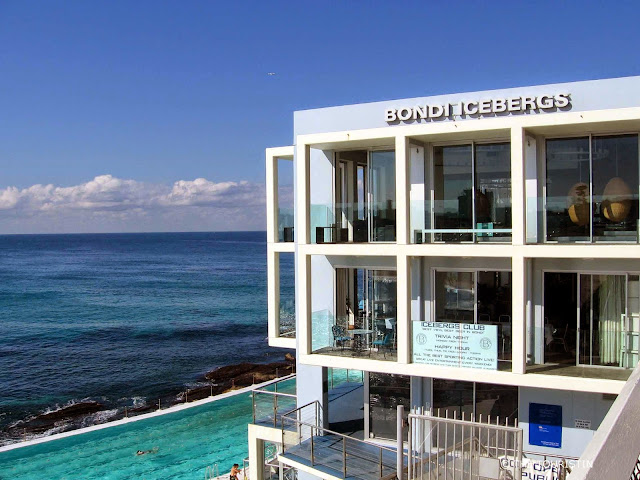 A large swimming pool next to a three-storey white cubic building with the name Bondi Icebergs with a view over the ocean.