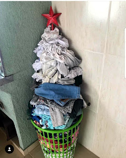 Foto. Em um canto da lateral de uma churrasqueira e a parede azulejada em bege, um cesto vazado de plástico verde repleto de roupas sujas empilhadas de maneira cônica, no alto da pilha, uma estrela vermelha estrategicamente colocada. O texto diz: Montei uma árvore de Natal pra minha mulher. Quase apanhei.