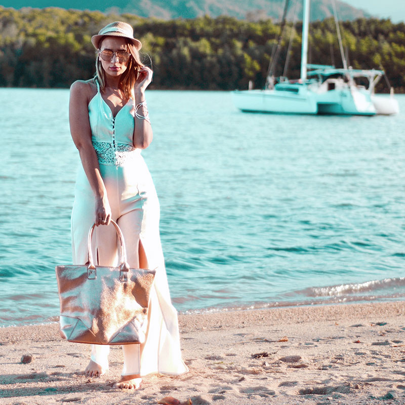 summer beach outfit white jumpsuit 70s flare leg rose gold sunglasses rose gold bag on beach