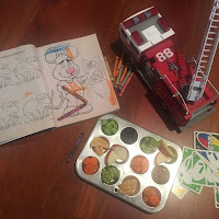 Photo of an aluminum mini muffin tray with snacks in each hole (carrots, celery, Romanesco, apple, dried cranberries, pecans) amongst kids' toys (fire engine with extended ladder, UNO cards, coloring book and crayons). https://trimazing.com/