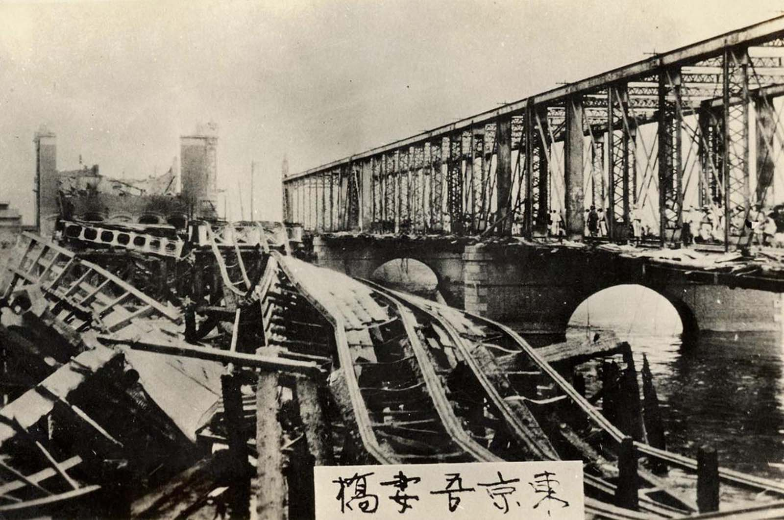 Collapsed Remains of the Azuma Bridge on the Sumida River. The wooden floor of the bridge burned down during the fires caused by the earthquake, leaving only the metal supports