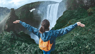 Chica visitando cascadas en su viaje por Islandia