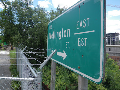 Photo of a green highway-style sign reading Wellington East and pointing to the right