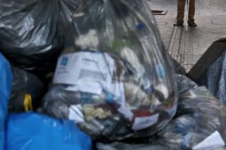 Σκουπίδια πάνω στη λωρίδα των τυφλών στο πεζοδρόμιο.
