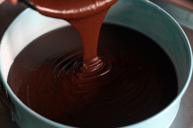 Chocolate cake batter being poured into a blue springform cake pan.