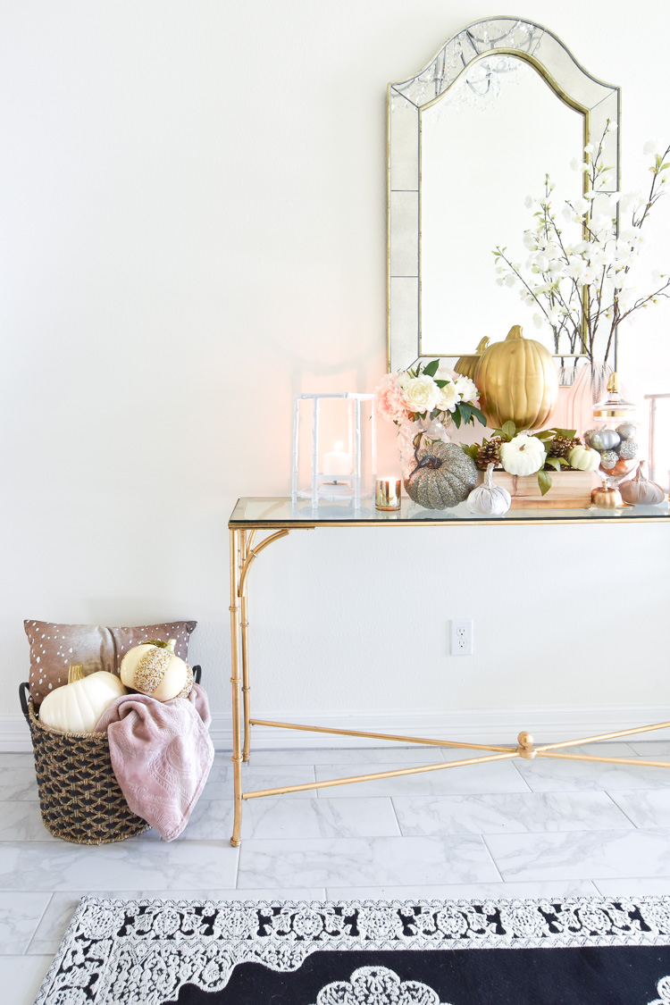 A white foyer goes glam with gold, blush pink and silver fall decor accents on a bamboo console table.