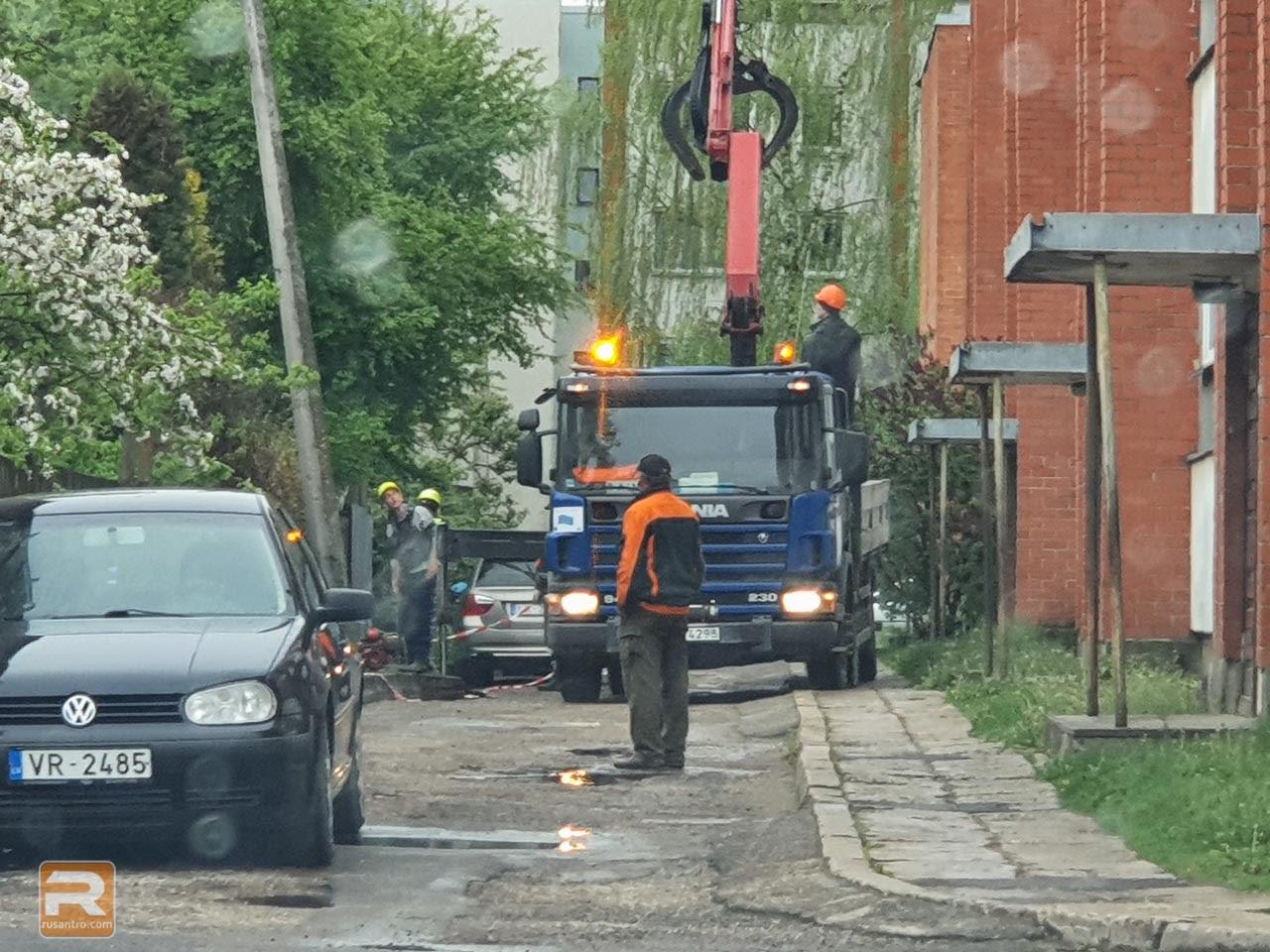 Vīrietis vēro, ka strādnieki demontē betona stabu