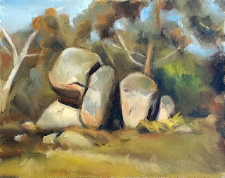 Oil painting of several granite boulders surrounded by eucalpyts.