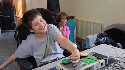 Happy looking boy in a wheelchair using a C-SID accessible game controller with switches to play a video game.