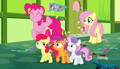 Pinkie bounces around the CMC as Fluttershy looks on