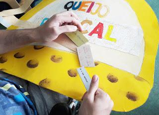 As mãos de um aluno a segurar as fichas da atividade dos provérbios