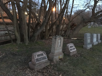Image is of the end of a row of stone grave markers of various heights. Behind them are trees and a bit of sunset.