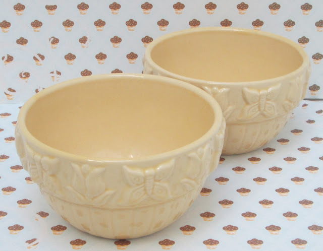 Two small yellow pottery bowls with cupcake background